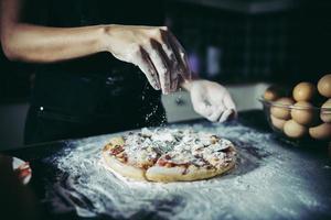 mani dello chef che versano farina sulla pasta cruda