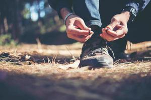 giovane escursionista allaccia i lacci delle scarpe mentre è in viaggio con lo zaino in spalla nella foresta