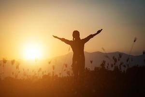 silhouette di una donna che prega su uno sfondo di bel cielo