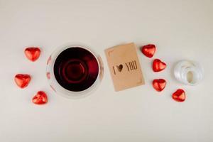 vista dall'alto di un bicchiere di vino con cioccolatini a forma di cuore e una carta foto