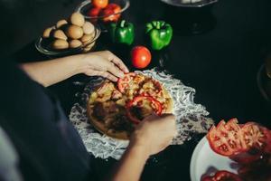 primo piano di una donna che mette condimenti sulla pizza fatta in casa