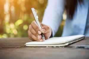 donna che scrive in taccuino foto