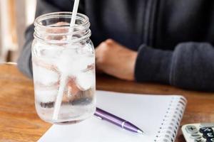 persona che tiene un bicchiere d'acqua in un barattolo