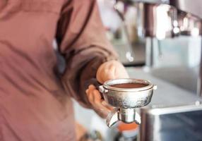 primo piano di una donna che tiene un macinino da caffè