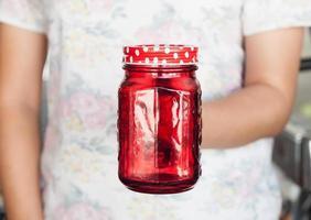 persona in possesso di un barattolo di vetro rosso