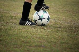 piede di bambino sul pallone da calcio