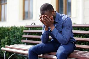 uomo stanco si siede sulla panchina fuori foto