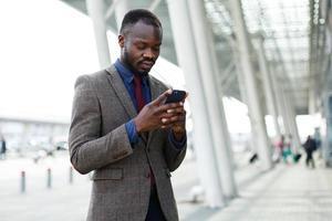 uomo d'affari che digita sul suo telefono foto