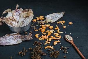 frutti di mare secchi posti su un tavolo di legno nero foto