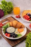 croissant, uovo fritto, condimento per insalata, uva nera e pomodori foto