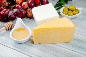 primo piano di formaggio con miele e altri antipasti foto