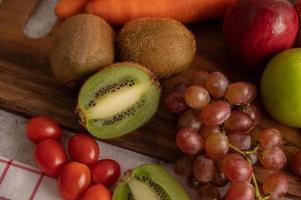 primo piano di kiwi, uva, mele, carote e pomodori foto