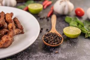vista laterale di semi di pepe in un cucchiaio di legno