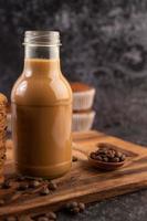 caffè in bottiglia con chicchi di caffè e muffin foto