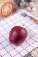 mela rossa su un canovaccio rosso-bianco