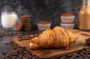 croissant su una tavola di legno con chicchi di caffè o. foto