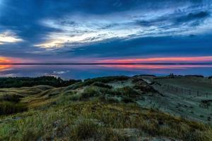 specchio d'acqua e dune durante il tramonto