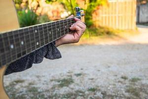 primo piano di una mano su una chitarra foto
