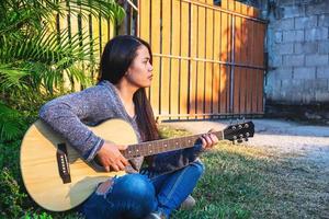 donna seduta fuori a suonare una chitarra foto