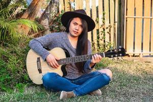 donna che suona una chitarra in un giardino foto