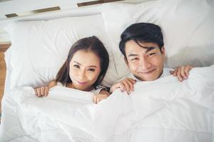 coppia felice posa insieme nel loro letto