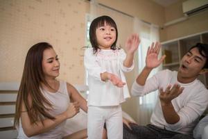 bambino felice con i genitori che giocano in casa foto