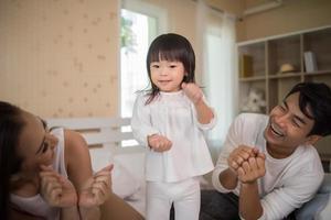 bambino felice con i genitori che giocano foto