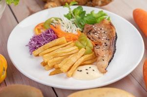 bistecca di pesce con patatine fritte e insalata foto