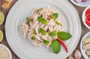 insalata di pollo su un piatto bianco con foglie di menta