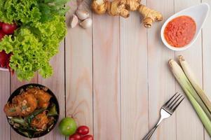 copia spazio di uno sfondo di legno con salsa, citronella, cipolle e zenzero foto