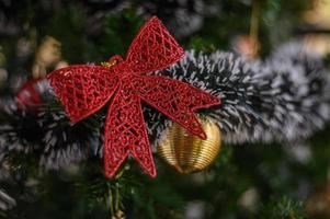 primo piano di un fiocco rosso su un albero di natale foto