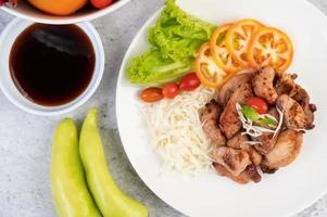 cotoletta di maiale alla griglia con pomodori e insalata foto