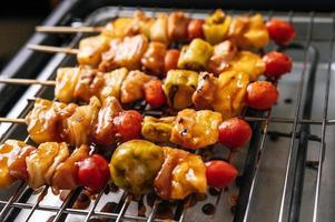 griglia per barbecue con una varietà di carni, pomodoro e peperoni