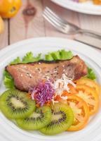 bistecca di pesce con patatine fritte, frutta e verdura foto