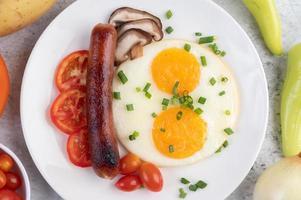 piatto della colazione con uova fritte, pomodori, salsiccia cinese e funghi