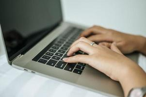 mani della donna che digitano sul computer portatile foto
