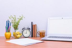 laptop, tazza e fiore sulla scrivania