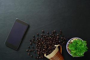smartphone e chicchi di caffè sulla scrivania, vista dall'alto foto