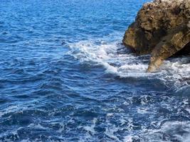 rocce e onde durante il giorno foto