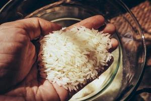 mani femminili piene di luce solare riso bianco e sfondo ombreggiatura. Close up varietà di riso al gelsomino bianco è la varietà principale della Thailandia per il consumo