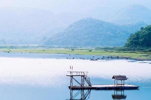 paesaggio di montagna del lago con riparo di bambù bungalow galleggianti incredibili e mozzafiato sul lago con sfondo di catene montuose. foto