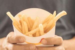 persona in possesso di patatine fritte