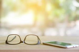gli occhiali sul telefono sono posti sul tavolo. cura degli occhi dalla tecnologia.