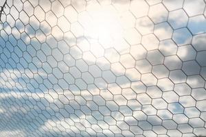 dettaglio della rete da calcio con la luce del sole sullo sfondo del campo, attrezzature da calcio