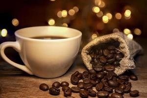 chicchi di caffè tostati, sacchetti e tazza di caffè bianco