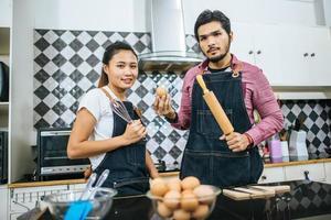 una giovane coppia felice che cucina insieme a casa foto