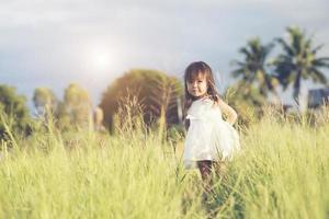 felice bambina in piedi nel prato in un abito bianco foto