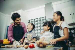 famiglia felice che gode del loro tempo cucinando insieme in cucina foto