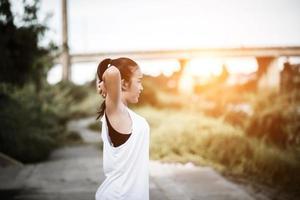 sana giovane donna in fase di riscaldamento all'aperto per la formazione foto
