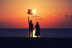 gli innamorati che guardano il tramonto con i palloncini foto